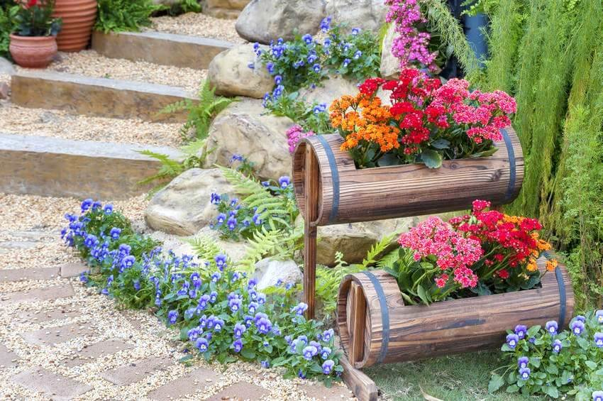 Пример дизайна клумбы в деревянных бочонках