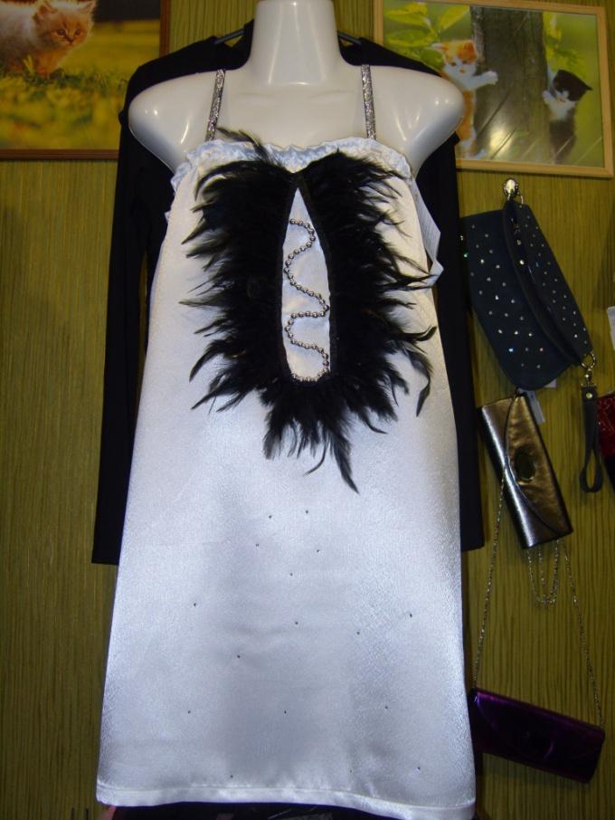 Модель из белого креп-сатина, украшенная черными перьями и стразами.