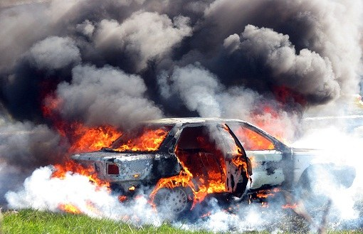 The car is enveloped in flames and smoke