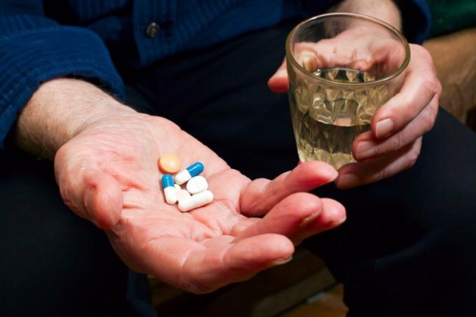человек собирается выпить таблетки
