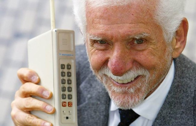 Martin Cooper with the first model of mobile phone