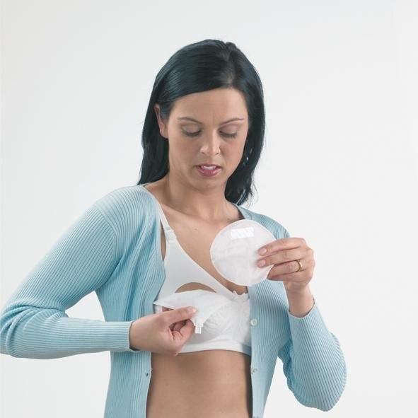 женщина вставляет прокладку для груди в бюстгальтер