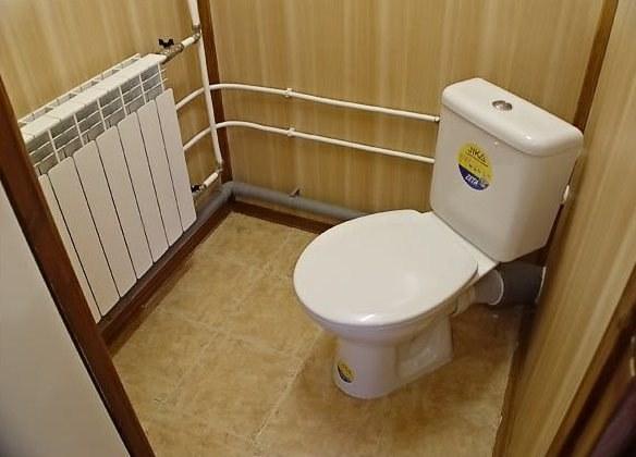 Туалет можно обшить пластиковыми панелями, вагонкой, ДСП