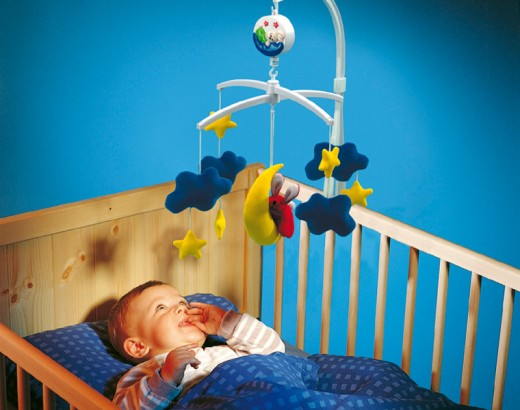 What age do I need to hang toys over the crib