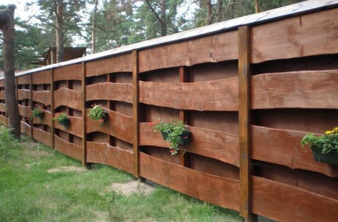 Забор, покрытый лаком, выглядит презентабельно