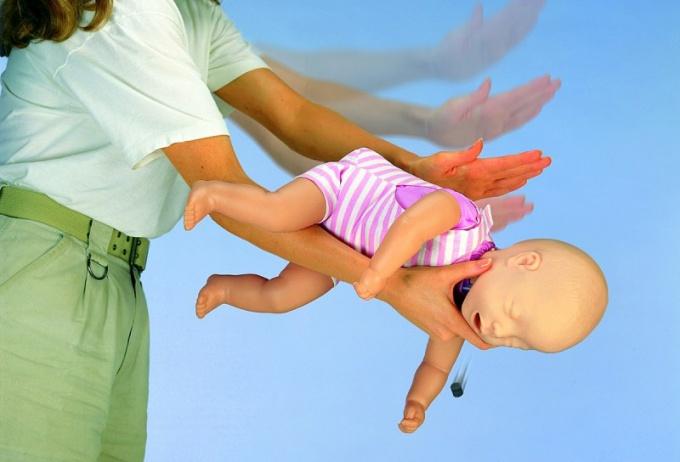 Если ребенок подавился каким-либо предметом, нужно повернуть его лицом вниз и несколько раз ударить ладонью между лопатками, чтобы удалить инородное тело