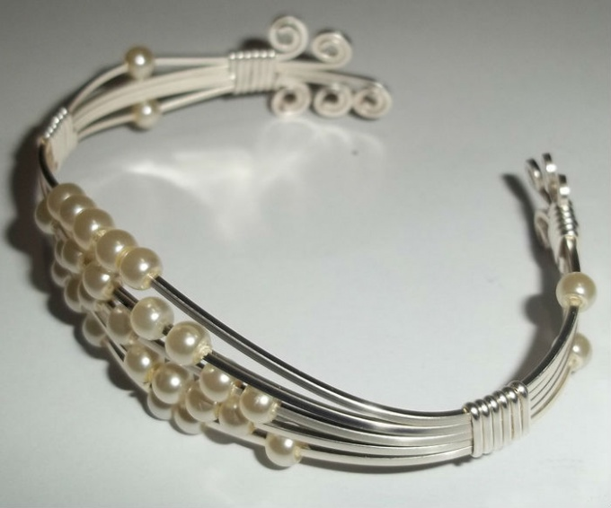 a bracelet made of beads and wire with their hands