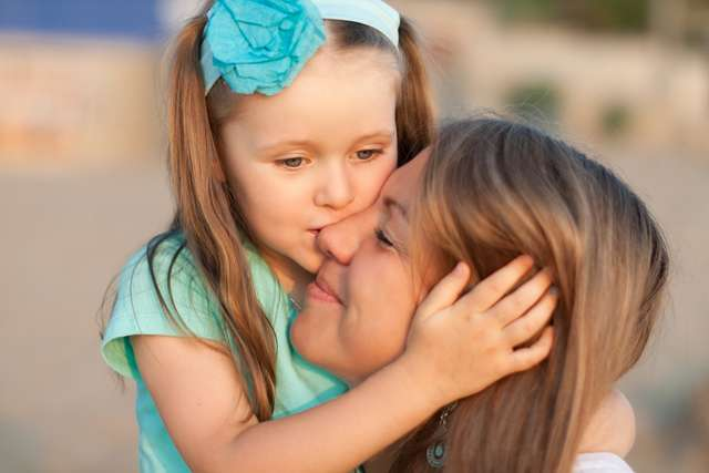 ребенок целует маму