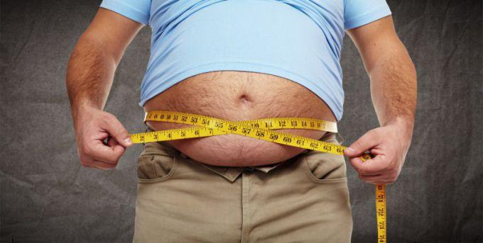 Девушка измеряет объём талии у мужчины