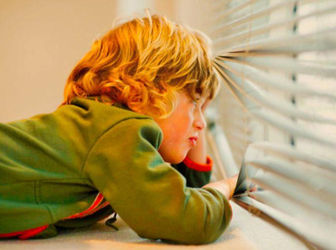 Ребенок скучает у окна
